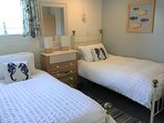 Twin bedroom: two full size adult single beds, ample clothes storage in wardrobe and drawers