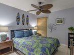 Second bedroom features queen sized bed and ceiling fan.