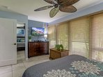 Master bedroom with flat screen television, plenty of closet space plus ceiling fan and window air condtioning.