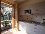 La cucina e la terrazza con la tavola apparecchiata.