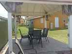Gazebo with patio furniture and lounge chairs.