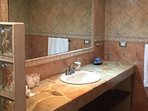 This bathroom has a full size mirror and stone counter top.