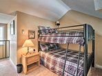 The space features a full bunk set, an extra twin bed and a Smart TV.