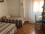 Habitación con cama doble más cama individual y un pequeño escritorio