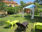 Jardín con cenador y tumbonas