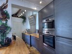 Breakfast bar leading into kitchen area equipped with high end appliances