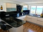 Fully fitted kitchen with breakfast bar and amazing sea views.