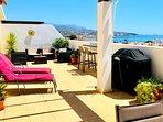 Stor terrass med matbord, sol stolar, loungedel, grill och ett barbord
