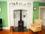 Kitchen has armchair log burner and TV