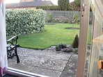 View stepping out of the patio doors; BBQ to right, gazebo ahead, side entrance has three steps up.