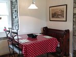 Eating area in the kitchen has a quirky church pew! Rise & fall lamp or candles  for the romantics