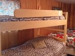 2nd bedroom with sey of single bunkbeds, and 1 double bed. Faces parking area and forest.