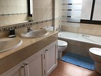 Family bathroom featuring double Roca sinks set in marble, bath, shower, toilet, bidet.