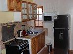 cocina con los utensilios necesarios., hervidor, licuadora, cafetera, refrigerador, microondas, etc.