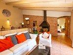 salón amplio con chimenea y cocina abierta