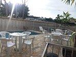 Area da piscina com cadeiras e mesas