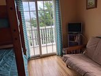 Third bedrooom, twin bunk bed and double futon, TV, opens to back balcony.