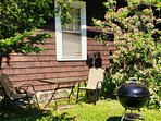 Outdoor table, chairs, and 22 inch Weber charcoal grill by your bedroom window