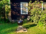 Outdoor area with a 22 inch Weber charcoal grill by your bedroom window