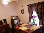 Dining area: high table &3 chairs, small fridge, microwave, coffee maker, kettle