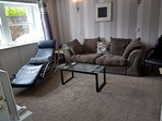 Living room - big comfy sofa, high arm chair and leather lounging rocker.