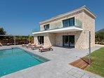 Infinity swimming pool and villa facade