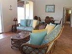 Grande sala soggiorno e sala da pranzo con porte scorrevoli in vetro per veranda coperta