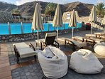 Heated communal pool with ample sun loungers, sofas, tables, chairs and bean bags.
