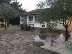 gîte et terrasse vus de la porte qui mène à la piscine