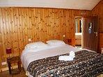 Master bedroom with original wooden walls and door to decking area.
