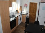 The kitchenette is at one end of the living room has cooker hob wash machine m/wave + fridge freezer