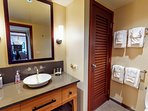 Bathroom 2 complete with bowl sink, large angled mirror, and towel racks.