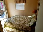 queen bed with sliding glass door that opens to wrap around deck