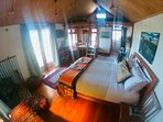 Queen bed in main living area and two singles in open loft above.