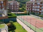 Urbanización con cancha de tenis y piscina al fondo
