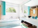 Salle de bain avec douche, grande baignoire, double lavabos et sauna
