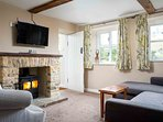 The cosy living room has plenty of traditional character, including exposed beams...