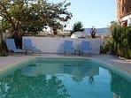 Het gemeenschappelijk zwembad met ligbedjes, zitje en barbeque.
