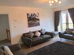 "Stunning 1st floor living room with balcony overlooking green. 55"" smart tv. Luxurious leather seats"