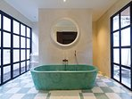 Turquoise themed bathroom with a stylish bathtub