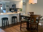 Bar height table for 4 in the dining area with extra seating at the kitchen island.
