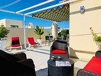 Vacker takterrass med loungegrupp, solstolar och matbord