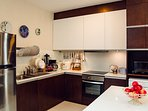 Overview of fully equipted Kitchen. You can see here: fridge, dishes, glasses, sink, oven, pan