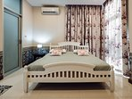 1st Floor. Bedroom 2. Kingsize wooden bed with TV, Aircond, private bathroom and entrance to Backyar