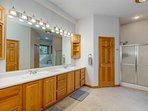 En suite master bathroom with two walk-in closets, double sinks, tub and shower