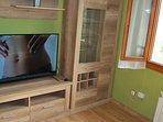 Salón con sofá-cheslong y tv plana grande