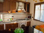 The fully equipped kitchen with large stove, oven, microwave, mocha coffe maker, kettle, toaster...
