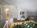loft area with foosball and flat screen tv and sleeper sofa