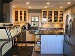 Renovated kitchen w woodstove. Soapstone counters, glass-top stove, dishwasher, fridge w/ ice maker.