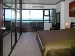 Large bedroom with king-size bed, sliding door wardrobe and sea view